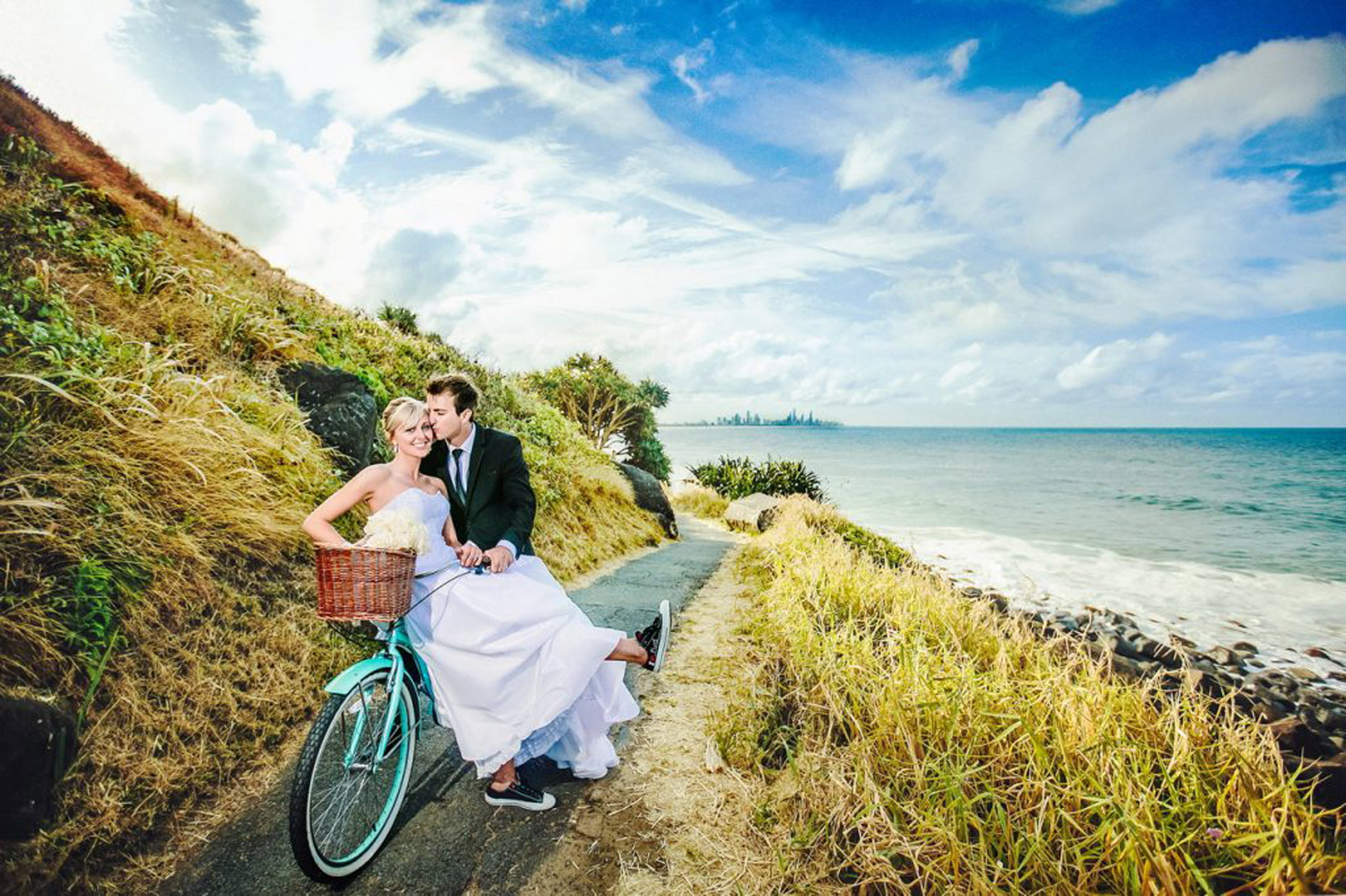 Wedding Couple riding a push bike with a rural countryside view